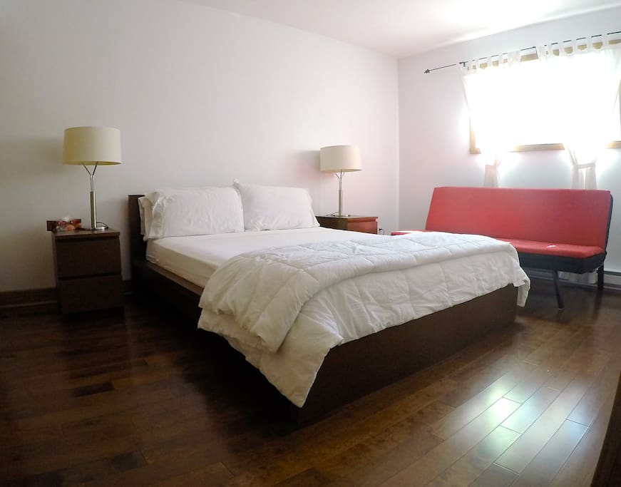 Large bedroom - Queen bed + Sleeper sofa, night tables with reading lamps, and spacious closets.