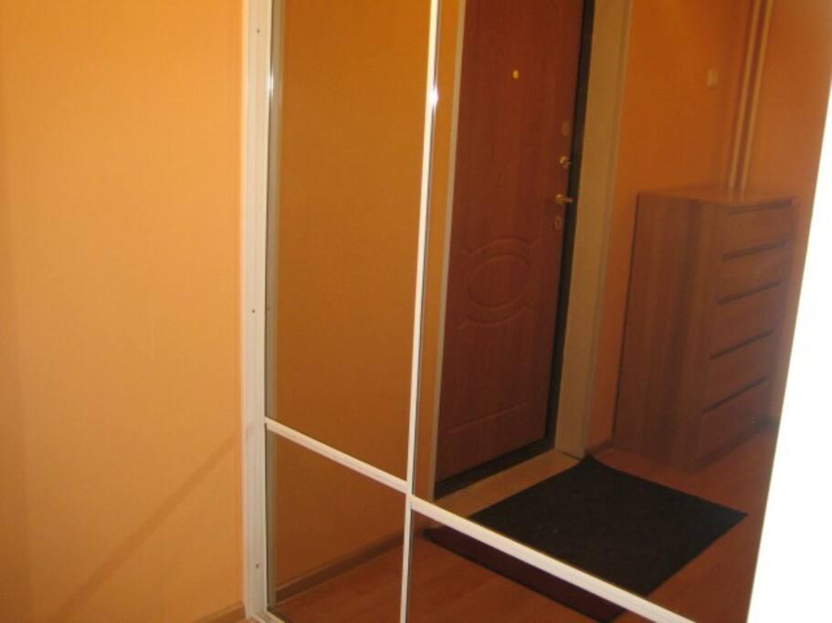 за раздвижными зеркальными дверями просторная гардеробная