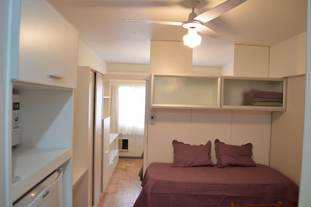 Vista desde la cocina hacia el estar/comedor. Un tabique divide el dormitorio con cama matrimonial.