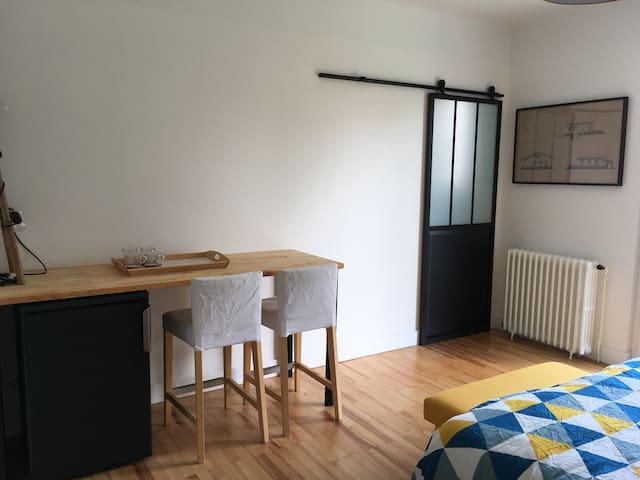 Une table/bureau avec réfrigérateur top. Accès à la salle de douche/WC par la porte verrière.