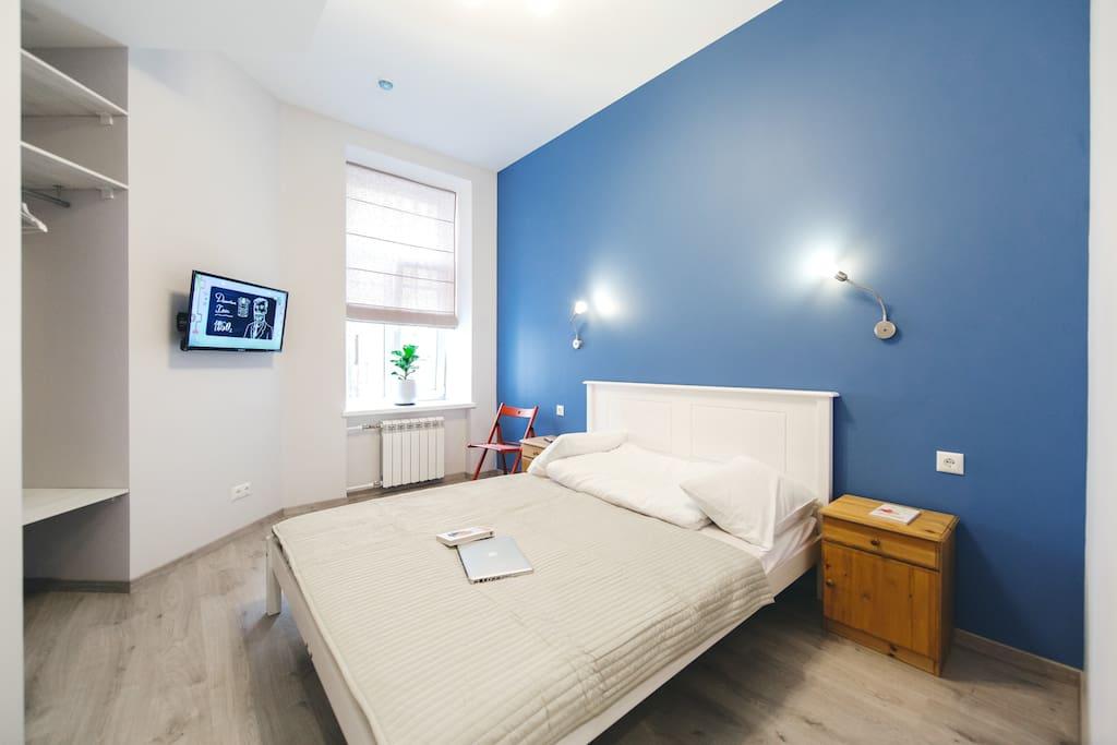 Общий вид номера. Зеркало, телевизор, удобные полки для верхней одежды, двуспальная кровать, журнальный столик.