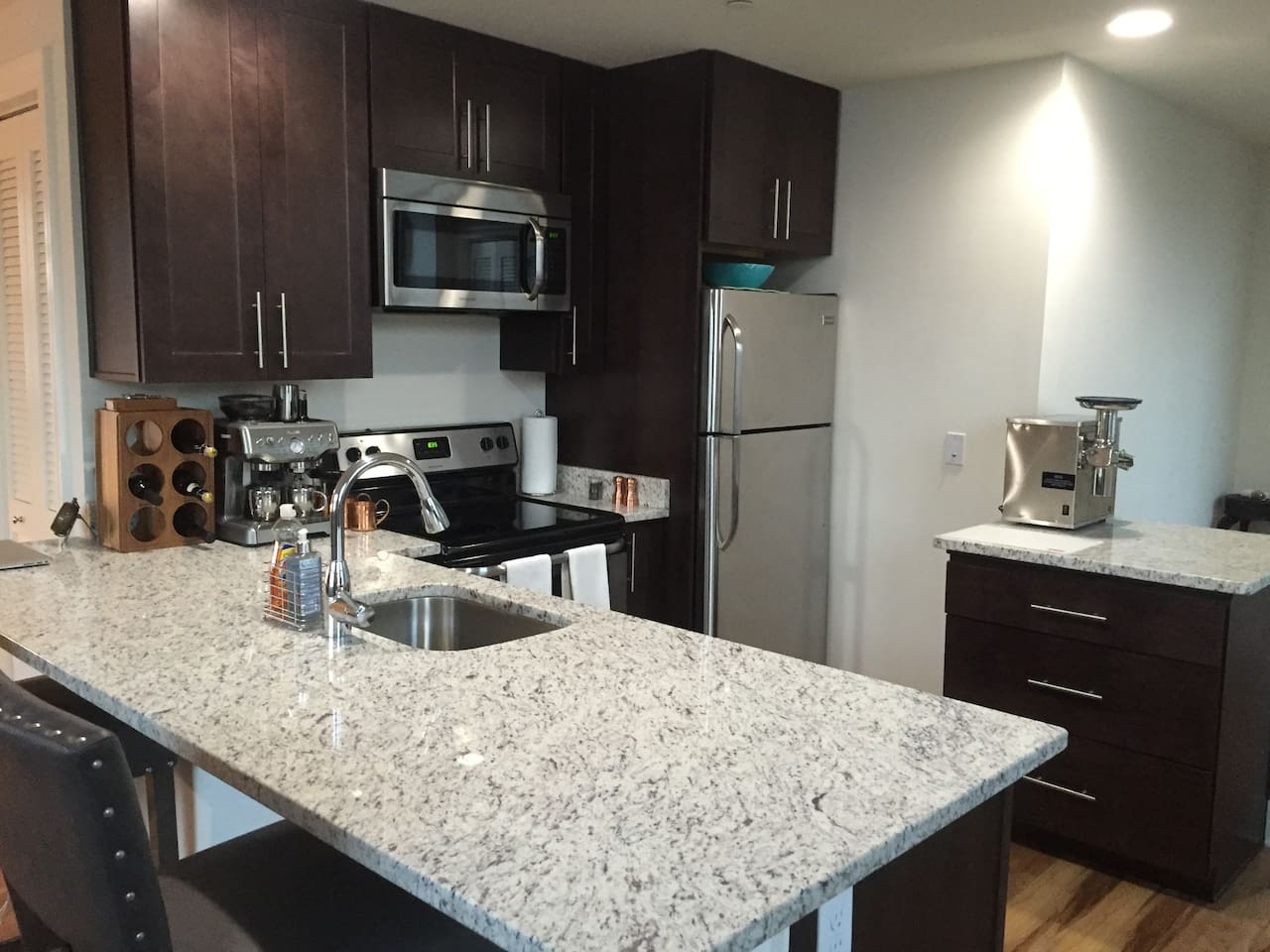 Open kitchen layout with granite countertops and stainless steel appliances including dishwasher.