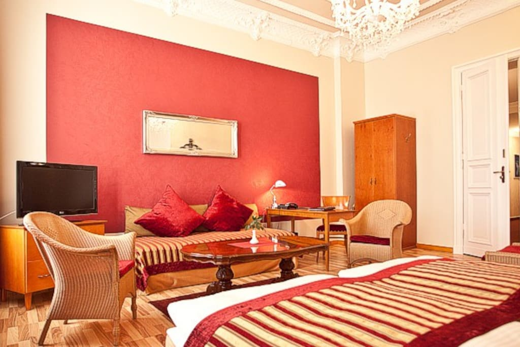 Hohe Decken, teilweise Flügeltüren und opulent gestaltete Stuckdecken