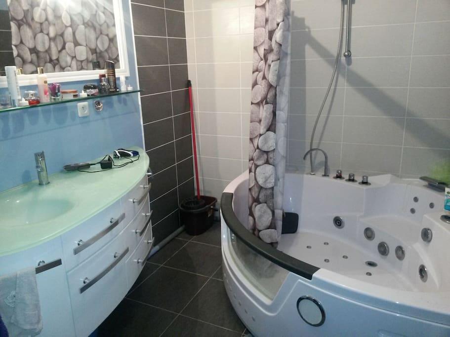 La salle de bain avec baignoire jaccuzzi