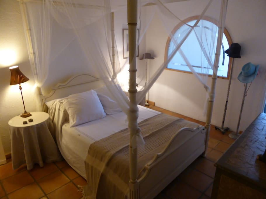Downstairs to master bedroom with four poster bed and WC