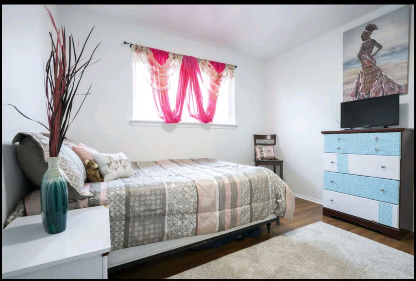 Private Guest Bedroom with full-sized bed, night stand, chair, rug, smart TV & tall dresser.