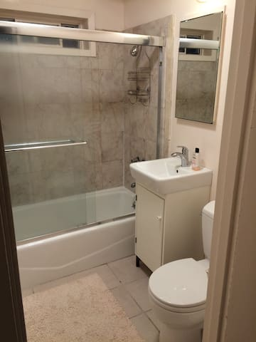 Step-in shower with tub, tiled floors and bathtub walls
