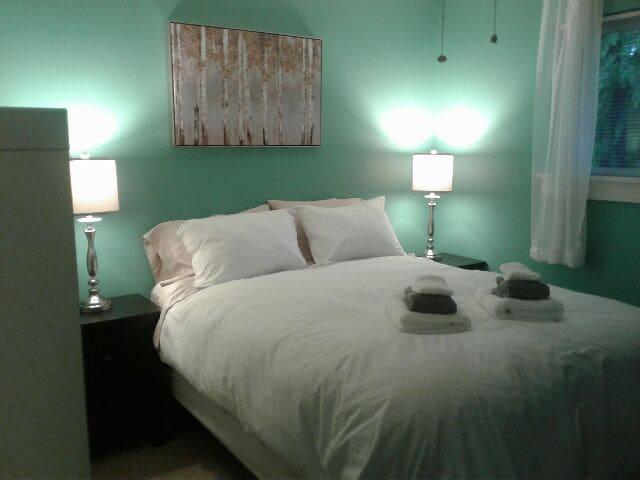 Queen size bed in master bedroom with ensuite bathroom