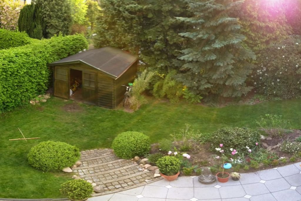 Blick vom Balkon auf  den Rasen und das Gartenhäuschen mit 2 Erwachsenen und 1 Kinderfahrrad