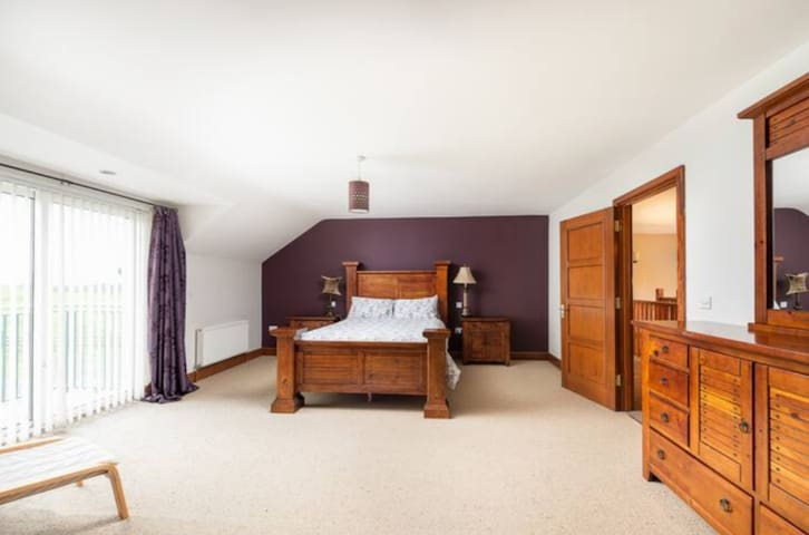 Master bedroom features full queen sized plush mattress on mahogany posts, a balcony overlooking farmland, and full en-suite bathroom.