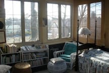 Sun porch with single bed, huge work table, windows on three sides