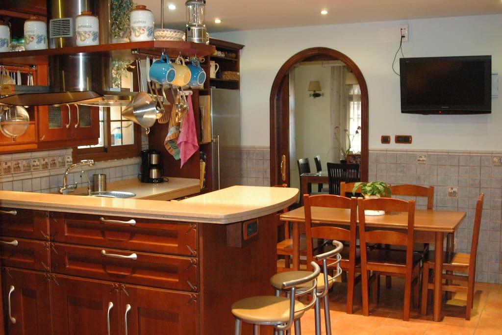 Cocina con office, barra y tv