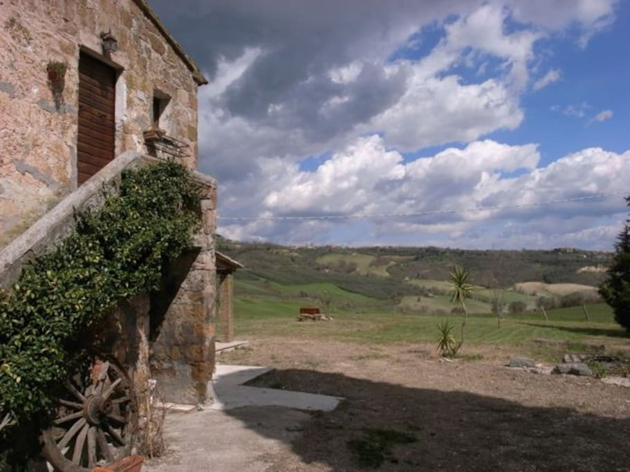 Side view of house with view of olive groves and countryside beyond.