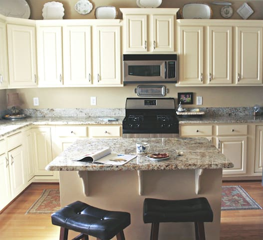 Enjoy your morning cup in this high-end kitchen featuring granite countertops and a gas range.