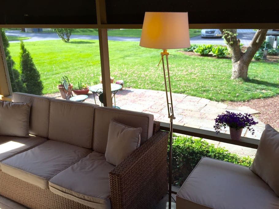 A screened-in porch has a TV and couch, and a sunny patio just outside.