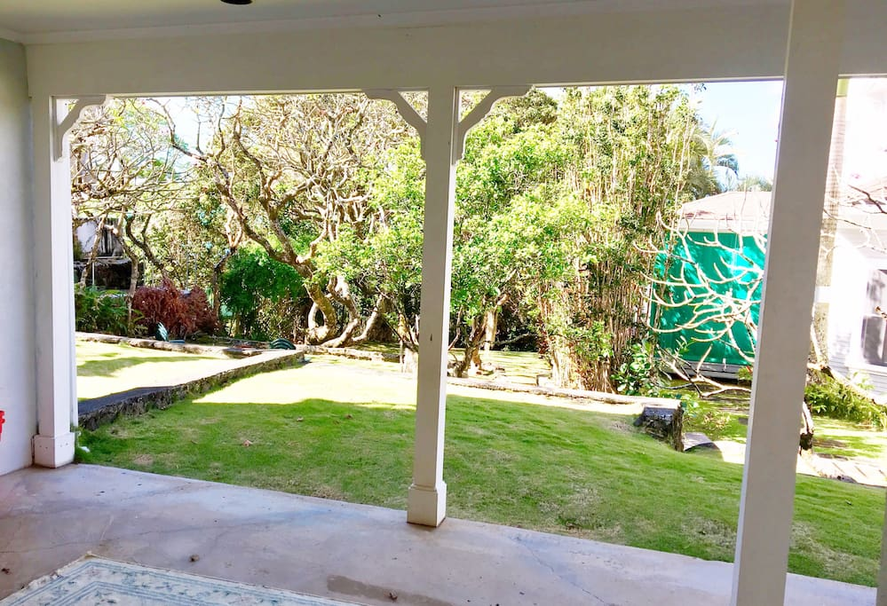 Covered lanai with view of the grounds of the historic residence.