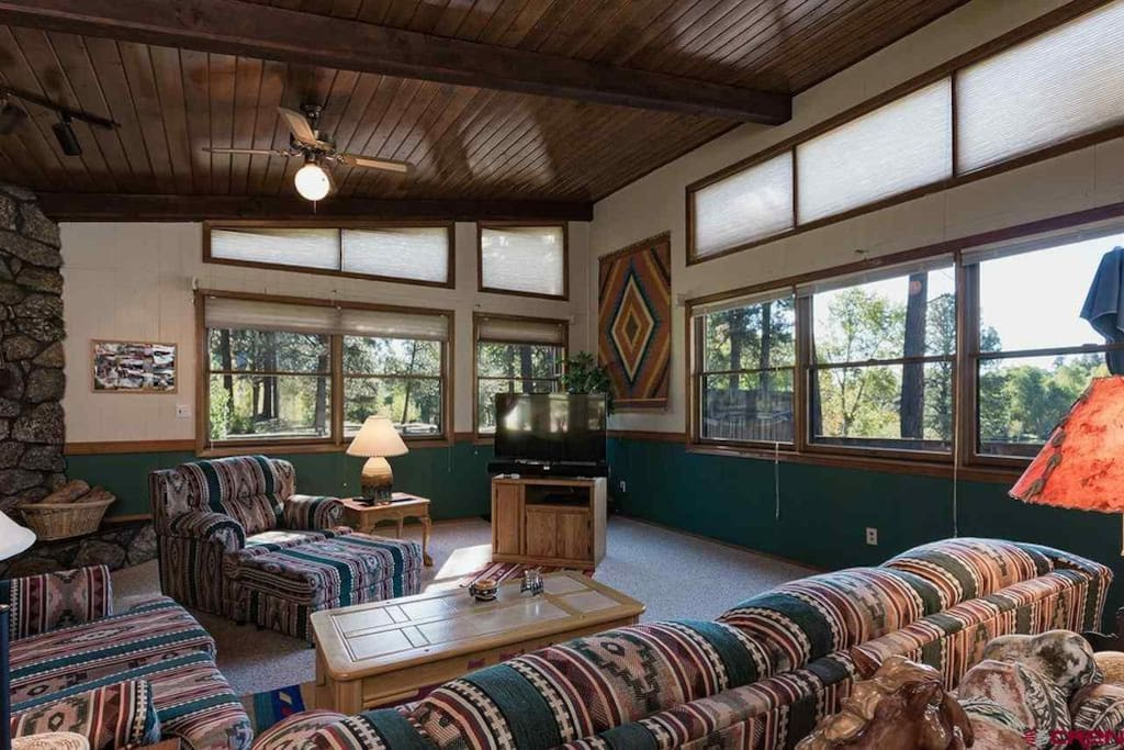Living room with fireplace. Looks out to front and side yards and overlooks pond.