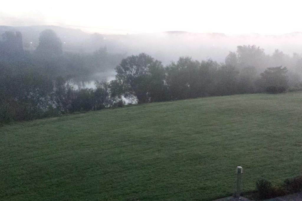 Early morning view with mist rising over the river.