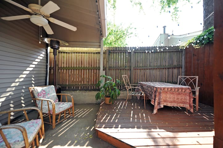 Private patio with table and chairs, hanging lights, an outdoor fan, and heat lamps.