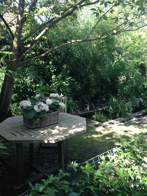 Petit jardin privé et clôturé avec étang. Table et chaises en teck, l'endroit ideal pour prendre le petit-déjeuner.