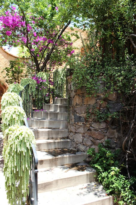 Charming curved stone staircase from upper street entrance, leading to casita.