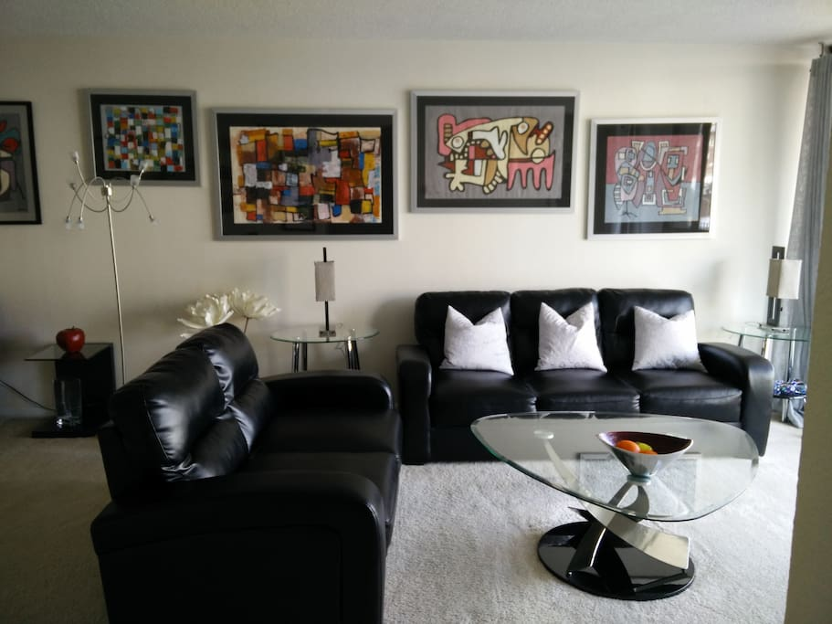SPACIOUS LIVING ROOM IS DECORATED WITH A COLLECTION OF ARTWORK