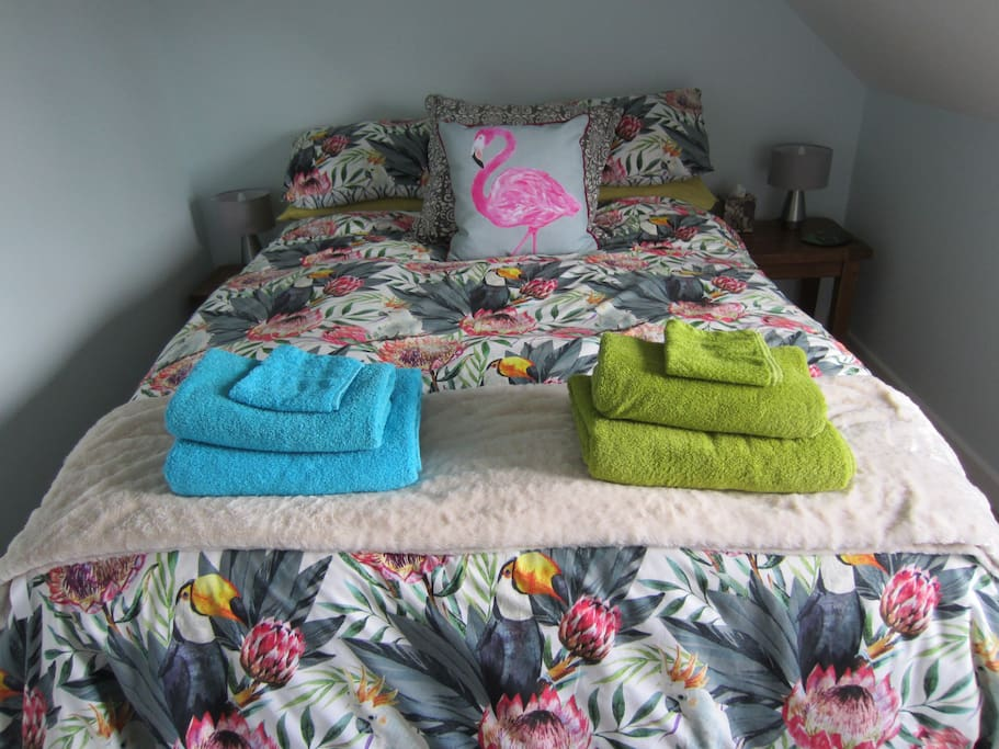 Comfortable, cosy double bed with bright, colourful towels