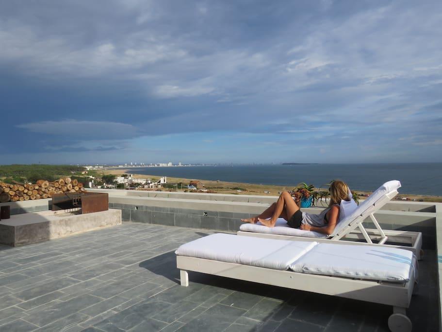 terraza muy amplia equipada con asador y camastros