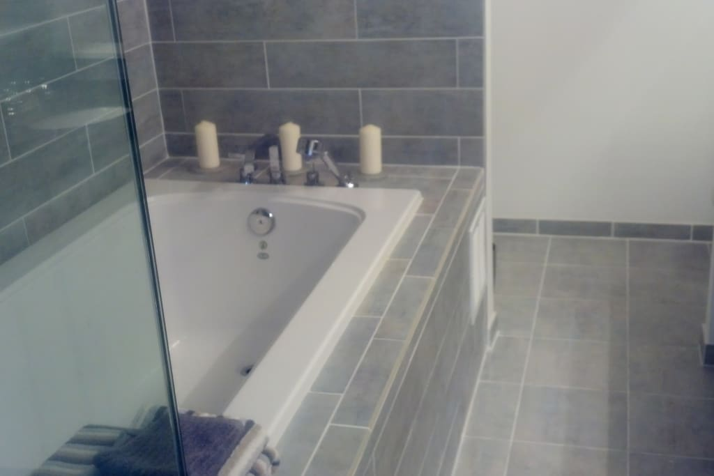 Master bath has stand up shower and large tub.