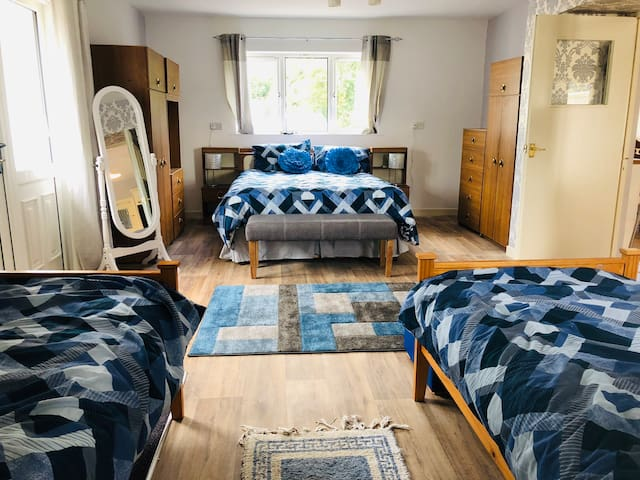 Family bedroom with a king size bed and 2 singles. This room has an en-suite bathroom with shower.