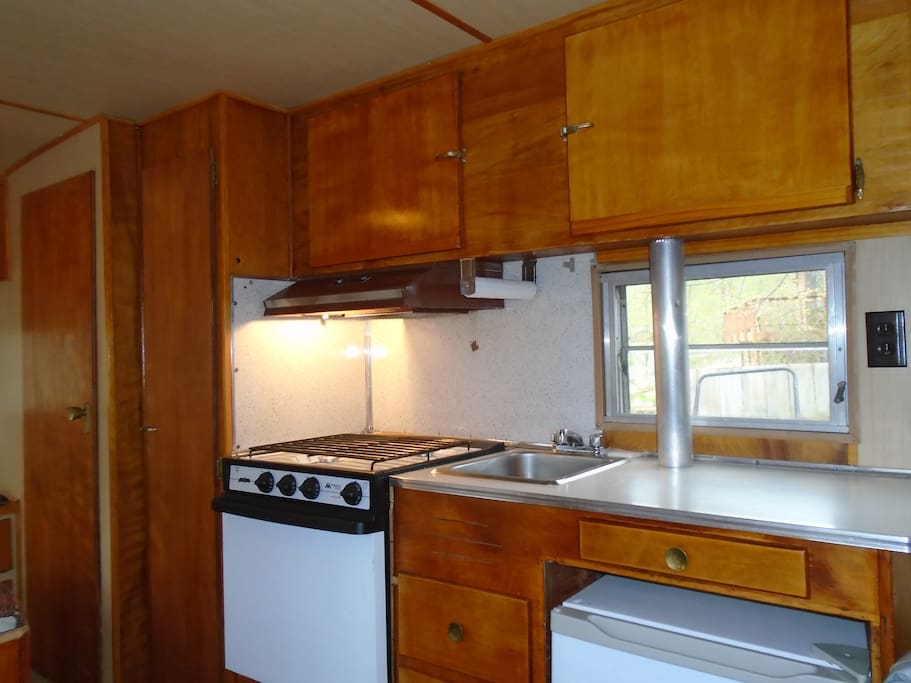 Propane Oven/Range, Sink and Electric Refrigerator.