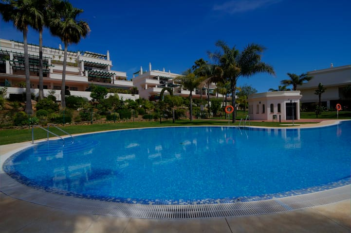 Large swimming pool in tropical gardens by the apartment