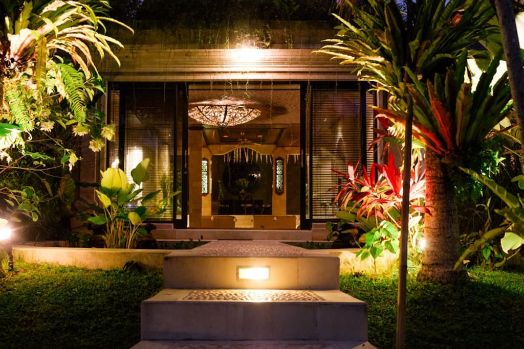 Night view across koi pond into TV Room. Outdoor soft ambient lighting throughout entire exterior of estate.