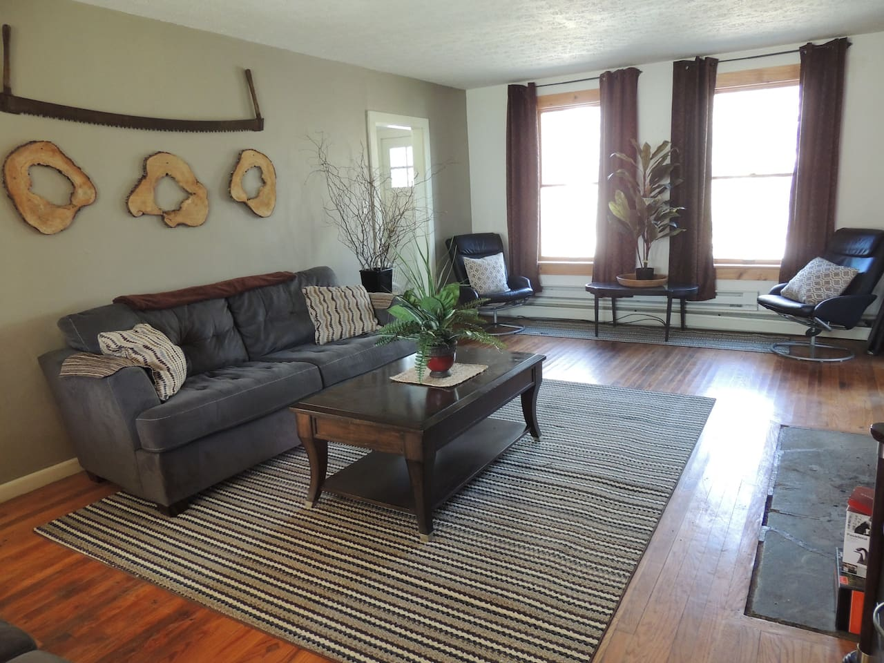 Bright, spacious living room looks out to the closed in porch. It has plenty of seating and a large flat screen TV.