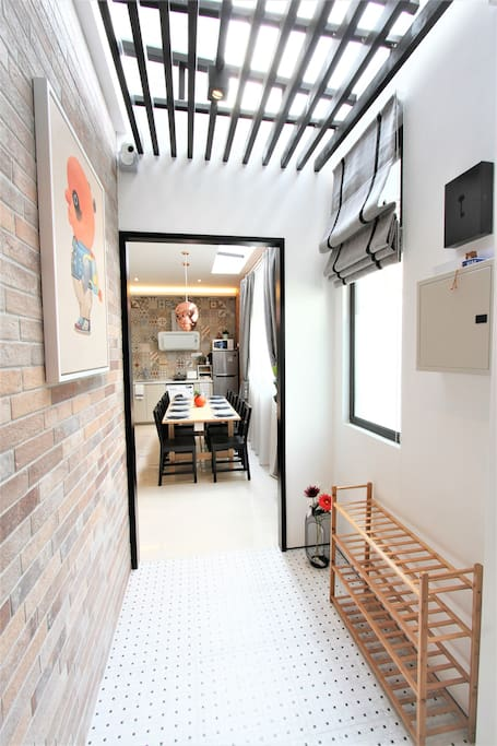 Entry way - Chic black/white floor tiles, craftstone bricks and ceiling louvers. A modern interpretation of traditional Peranakan heritage houses!
