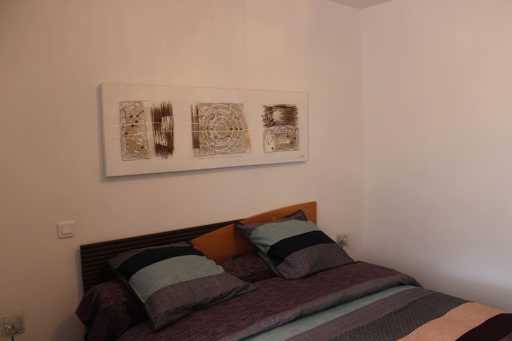 Chambre avec 1 grand lit et une armoire.