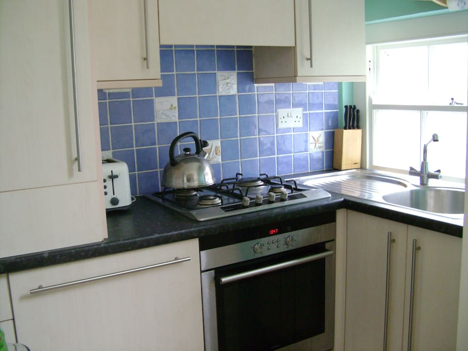 Galley kitchen with electric oven, gas hob, fridge freezer and dishwasher.