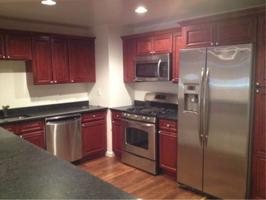 Huge kitchen with stainless steel appliances, dishwasher, plenty of cabinets, and counter space.