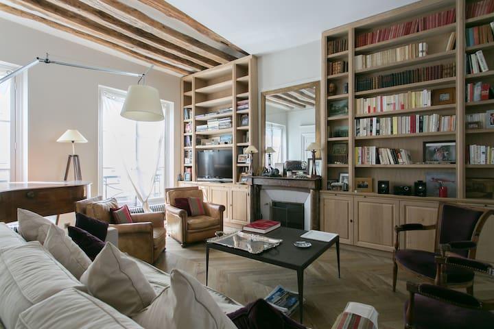 Le salon avec sa grande bibliothèque et son piano.