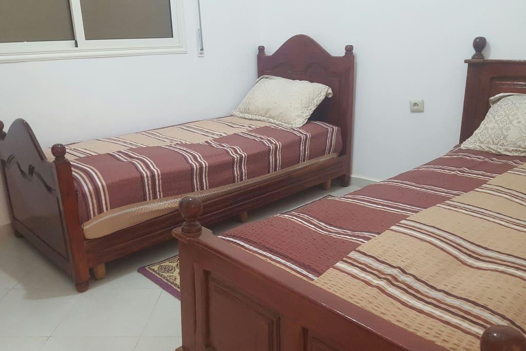 chambre équipée de 2 lits en bois