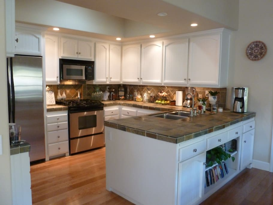 Kitchen features slate counters, recessed lighting and stainless appliances