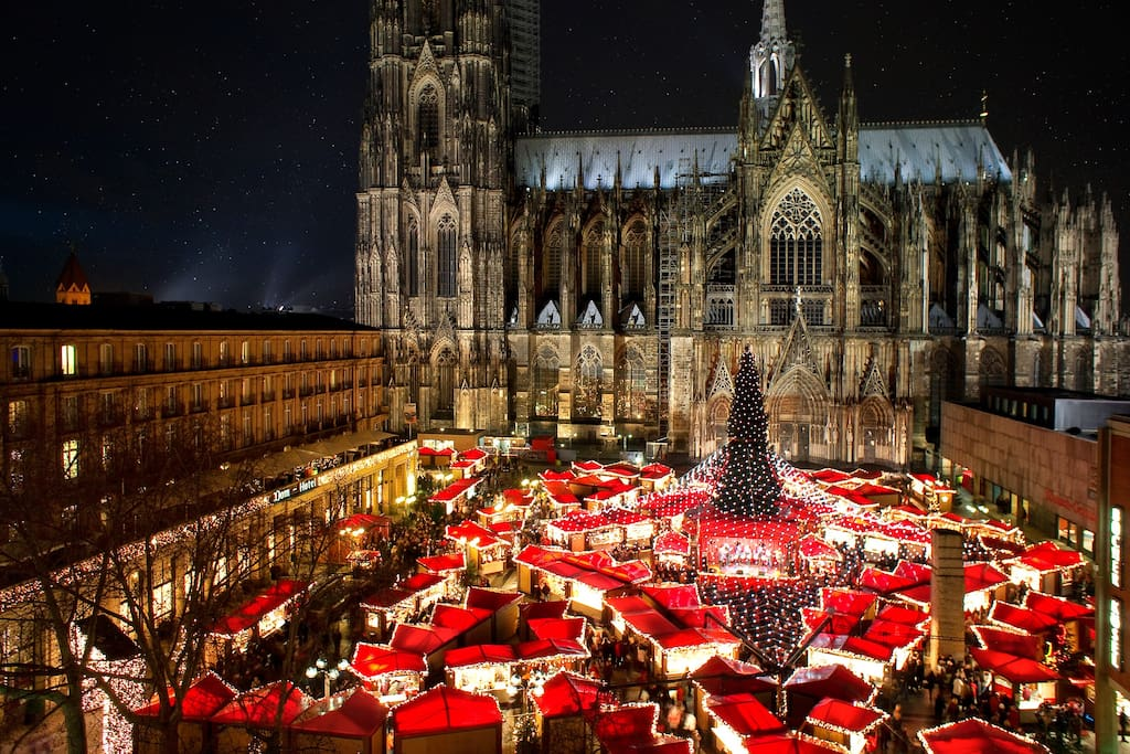 The famous Cologne Christmas Market with its star shape, the big natural christmas tree and the beautiful illumination. View on the christmas market with gothic Cologne Cathedral in the Background.