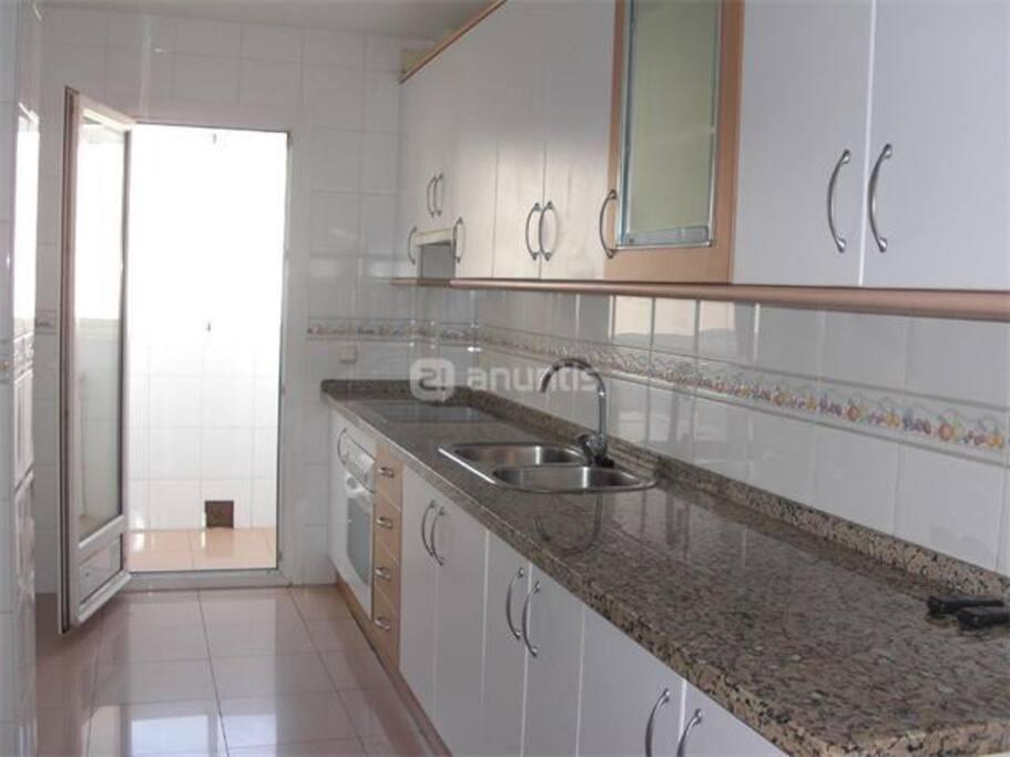 Cocina, equipada con horno, vitrocerámica, microondas, lavadora, frigorífico grande, y útiles de cocina. No tiene ni lavavajillas ni secadora