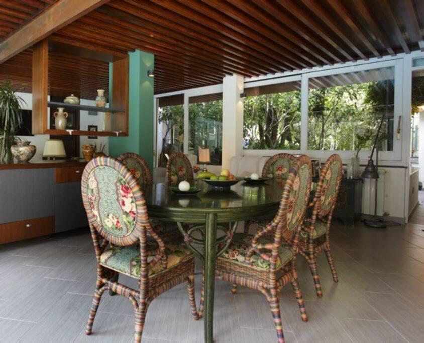L'angolo pranzo del living con vetrate sia sulla piscina che sul rigoglioso giardino retrostante