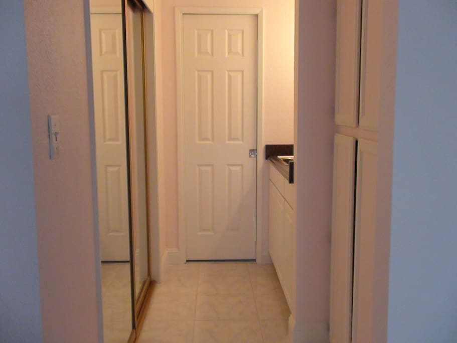 Hallway with a large closet, cabinets and pantry with deep sink that leads to the private bathroom.