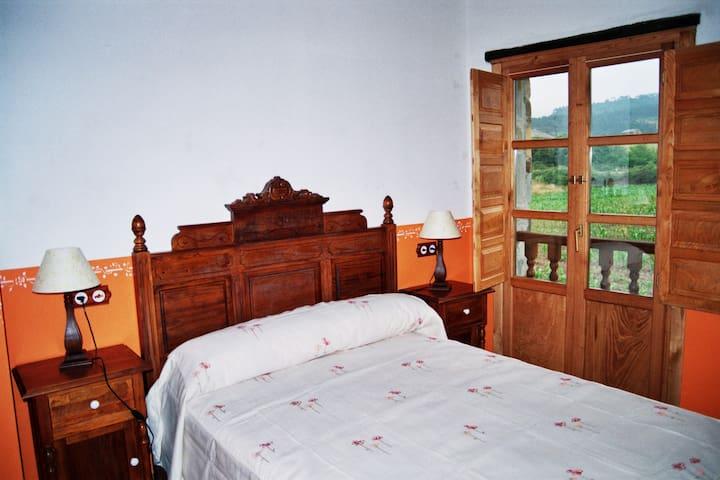 Habitación con cama doble y vistas llenas de vegetación.