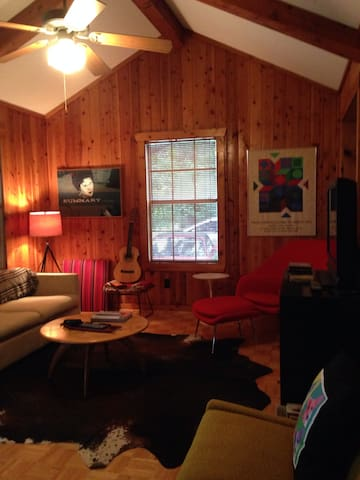 Inside the cabin is a cozy lounge with classic Mid-Century furnishings, and cable television, DVD player, and Roku--just in case the guitar isn't operational that day.
