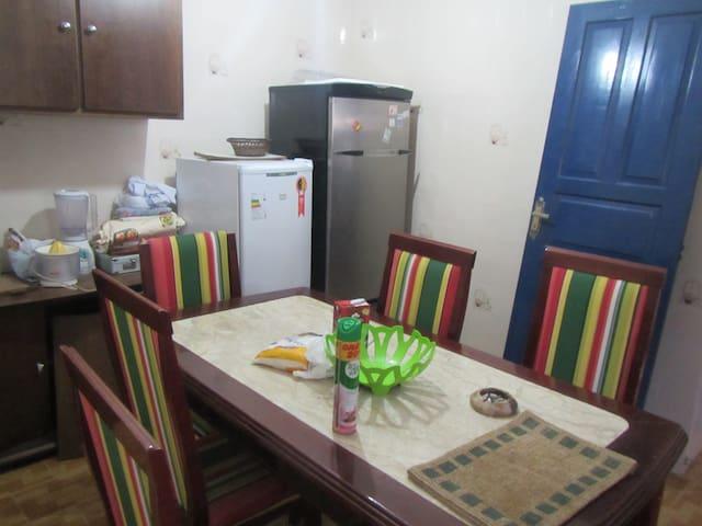 Parte da cozinha com elétricos domésticos e mesa com 6 cadeiras.