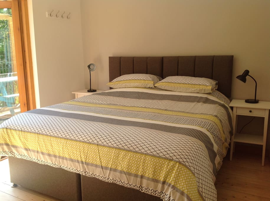 Bedroom with king size bed & patio doors opening on to the decking.