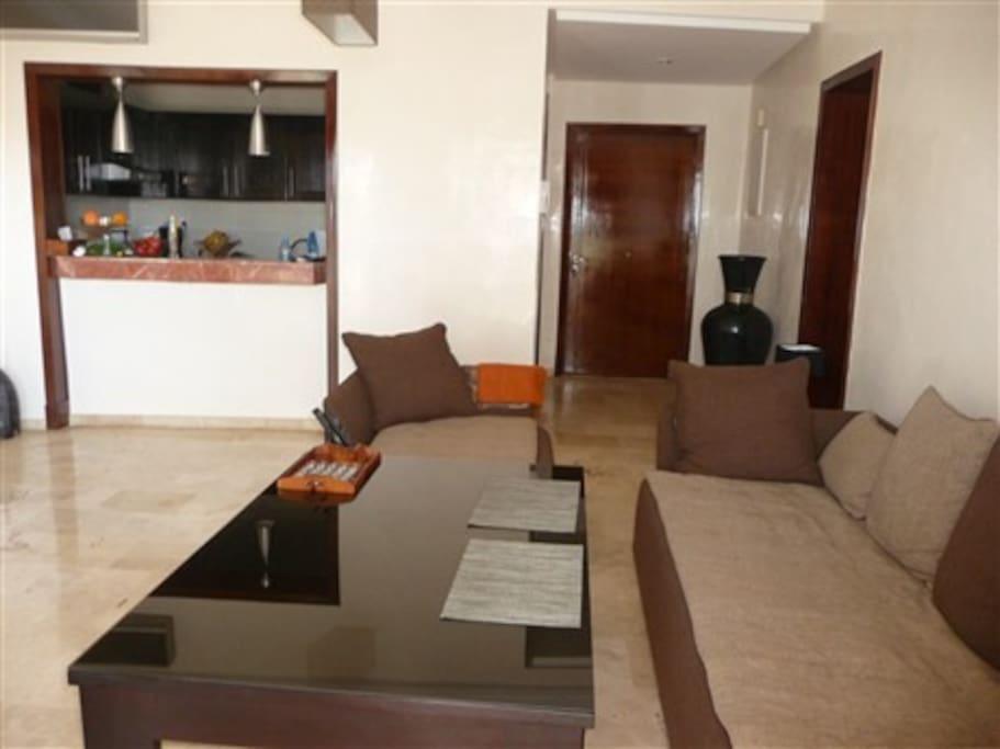 accès direct à la terrasse, marbre au sol, canapé et table de salon touareg, table à manger,  télé, lampes, rideaux marocains...